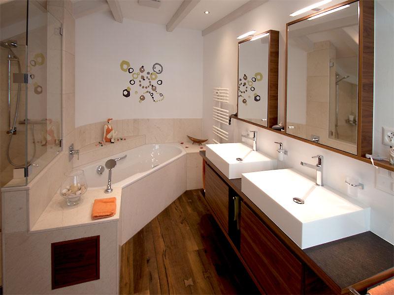 Ein Bad mit Holzboden und Holzkommoden